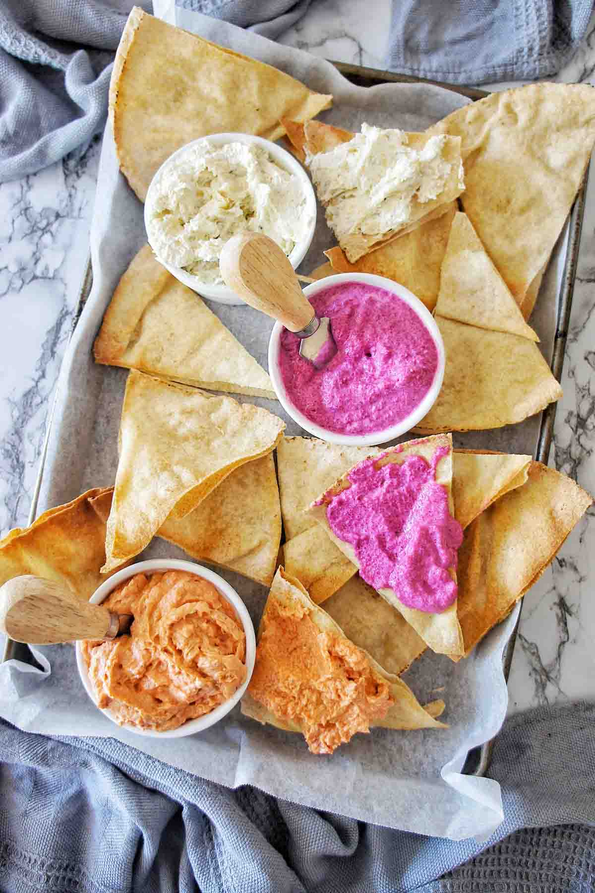 Dip platter with pita chips and 3 dips on a large platter