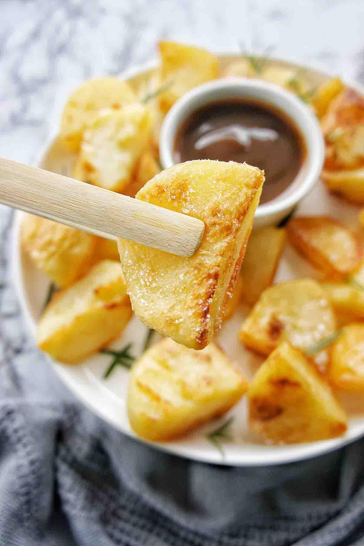 Tongs holding crispy roast potato above a white plate