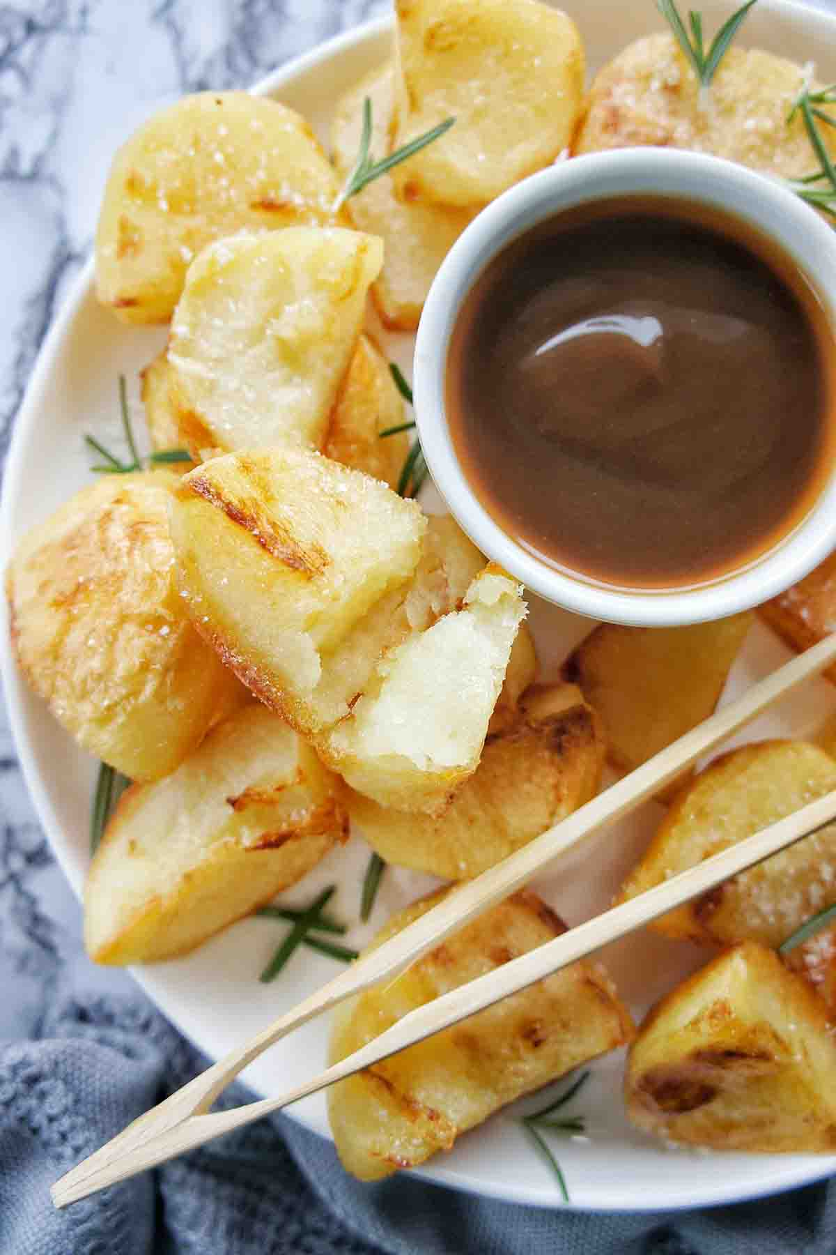 Crispy roast potatoes on a plate with a small bowl of gravy