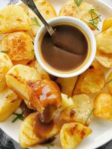 Duck Fat Roast Potatoes on a white plate with a small bowl of brown gravy