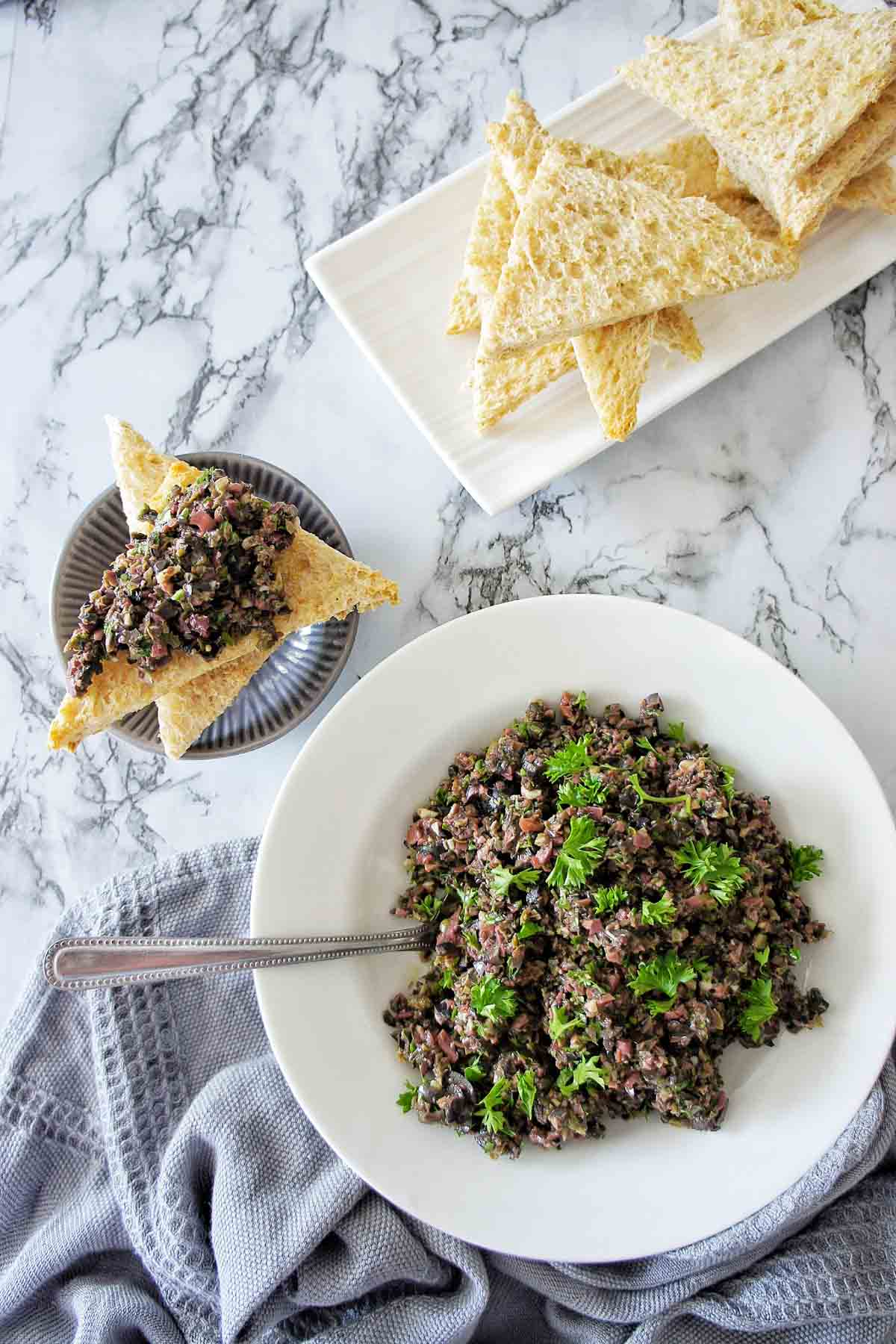 Black Olive Tapenade on toast points with a bowl of tapenade to the right