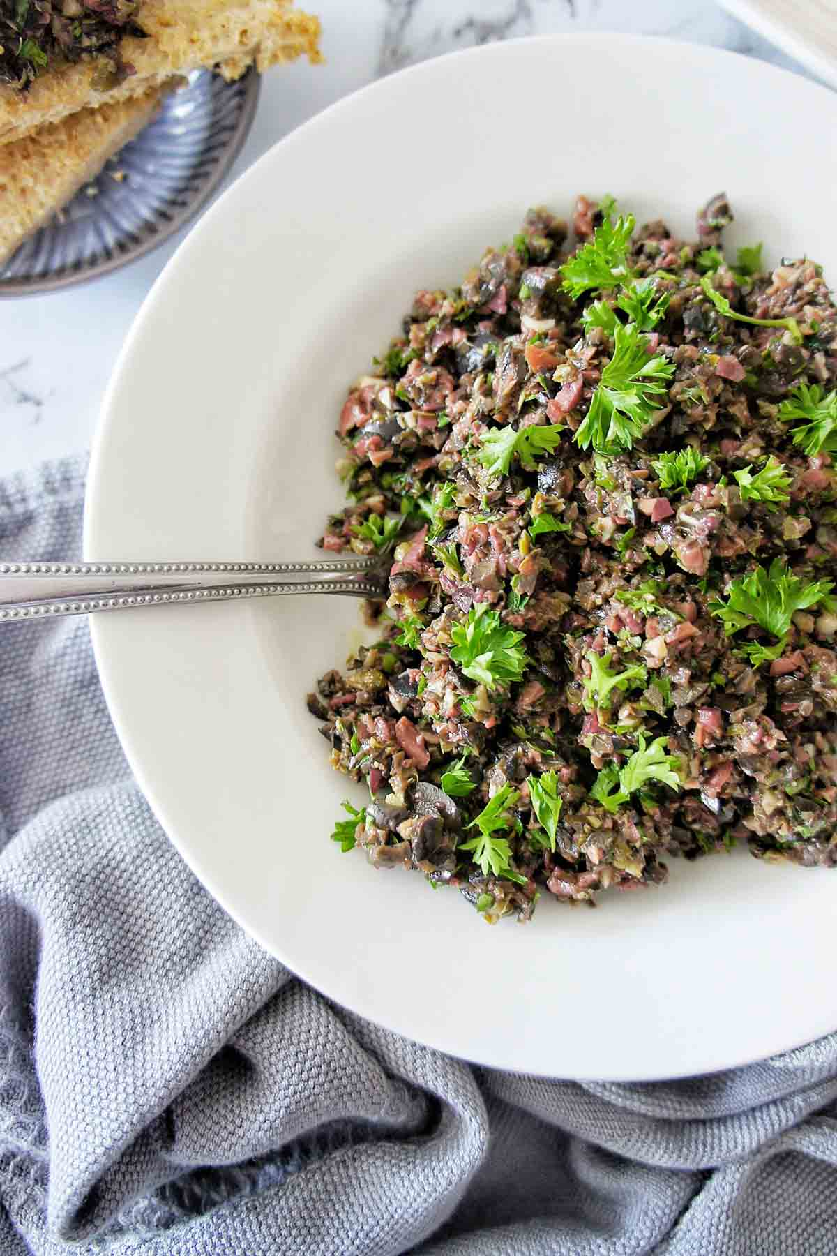Easy black olive tapenade in a white bowl with spoon to the left