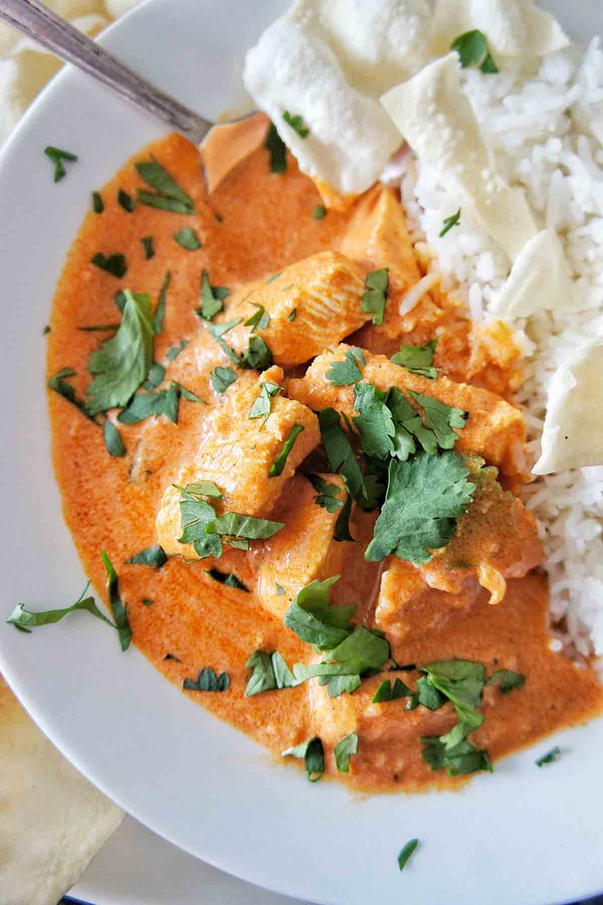 Easy Butter Chicken in a white bowl with rice and coriander