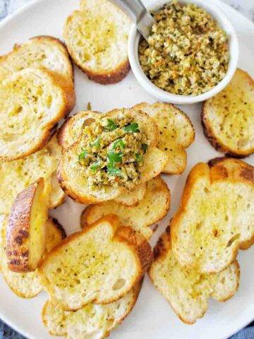 Crostini with on a white plate with small bowl of tapenade at the top