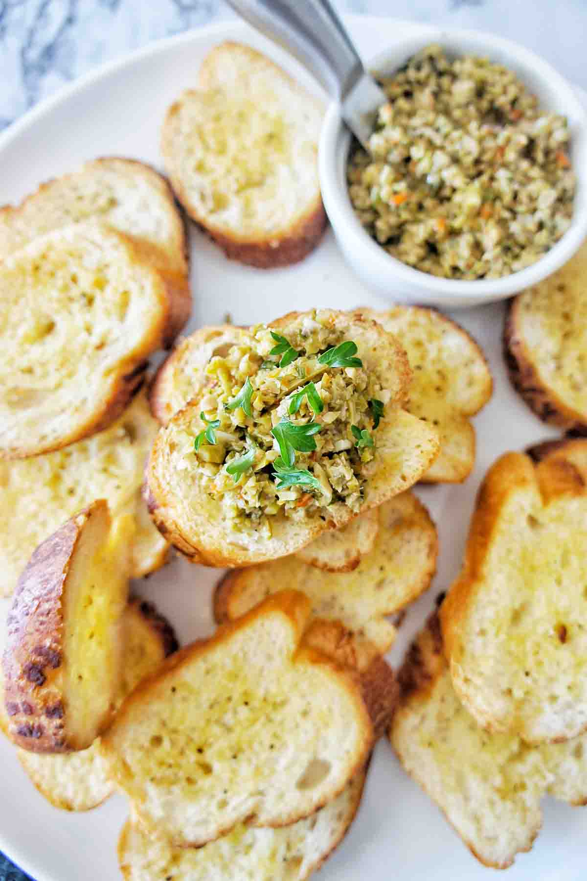 Crostini on a white plate with some plain and 1 with tapenade topping