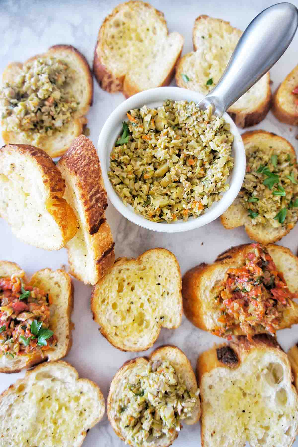Crostini with tapenade on a white background with dip bowl top centre