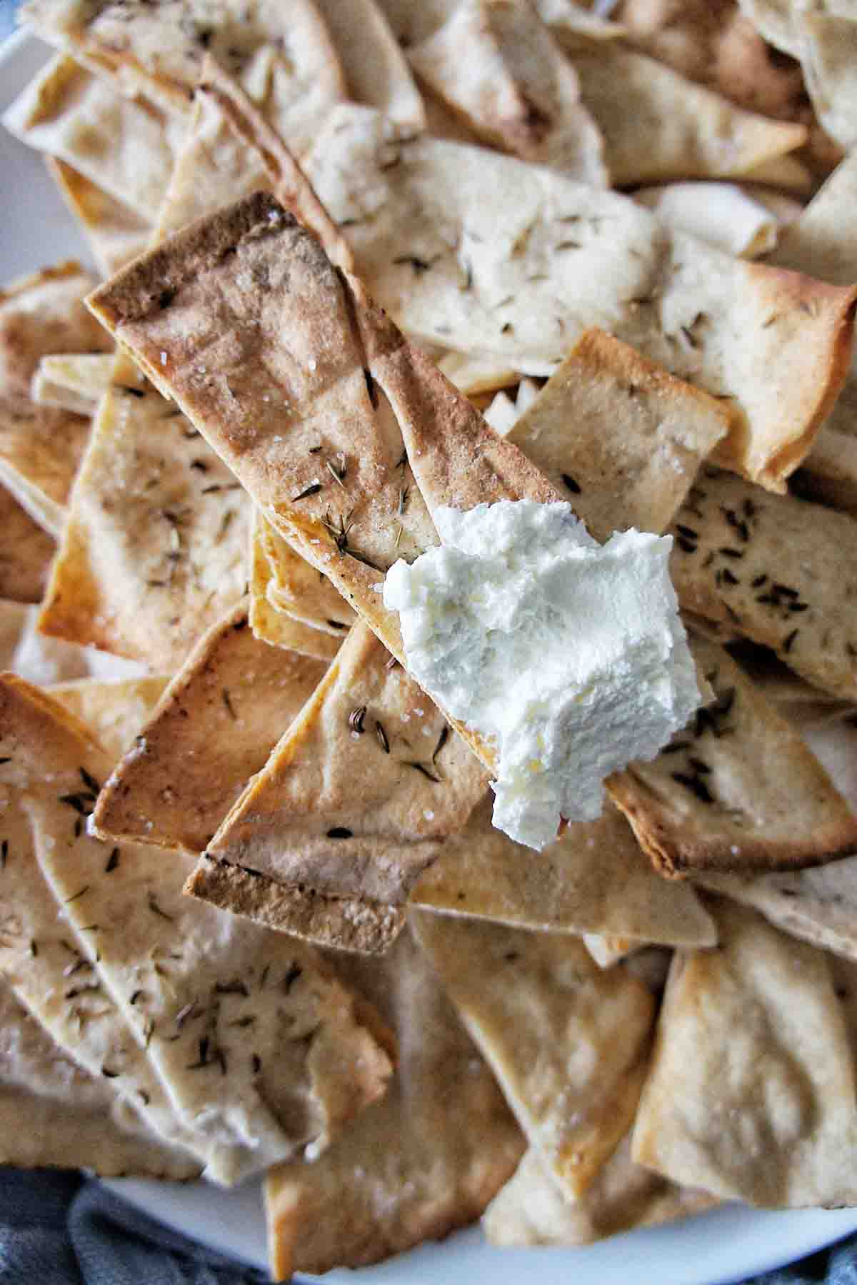 Pita Chip with white dip on one end on a plate full of chips
