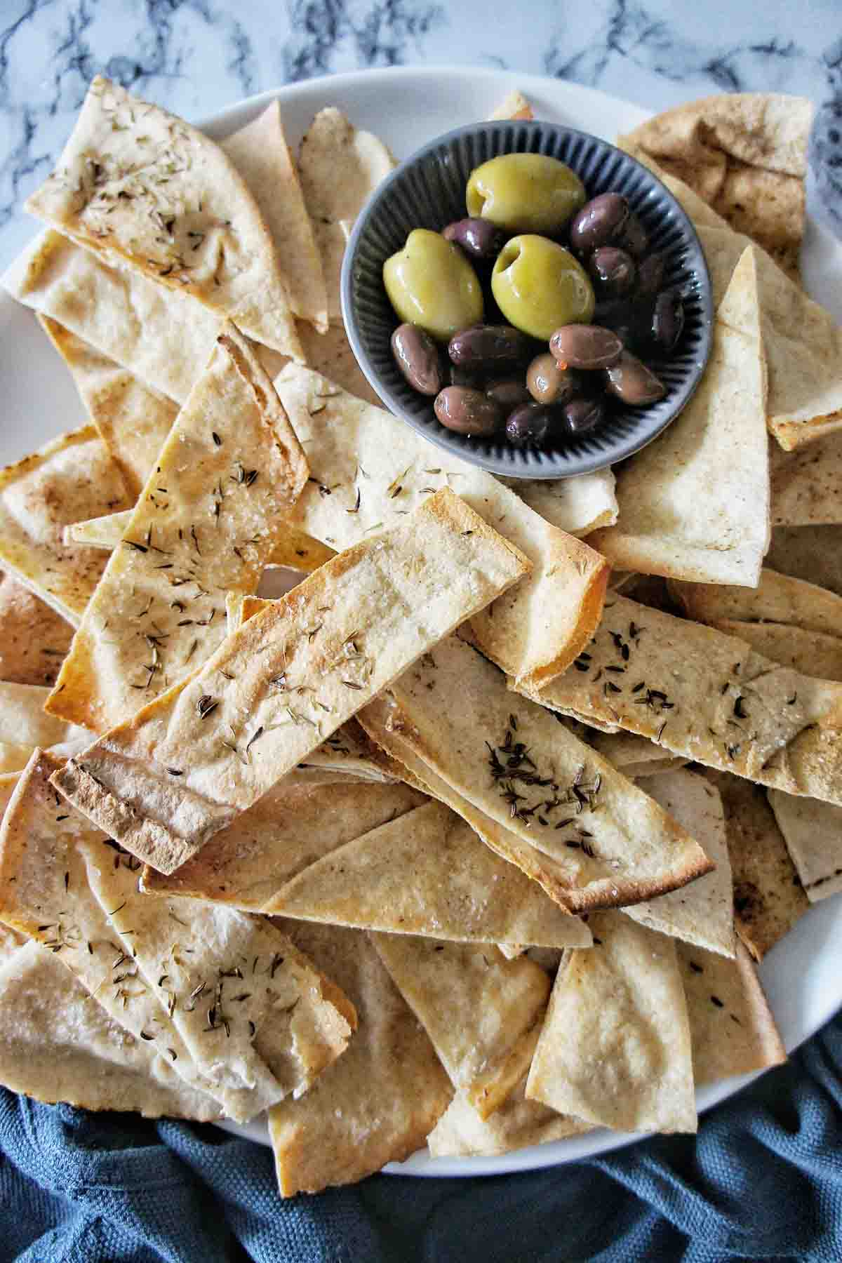 Oven Baked Pita Chips with dried herbs on a white plate with olives