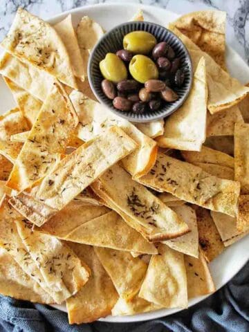 Homemade Pita Chips on a white platter with olives