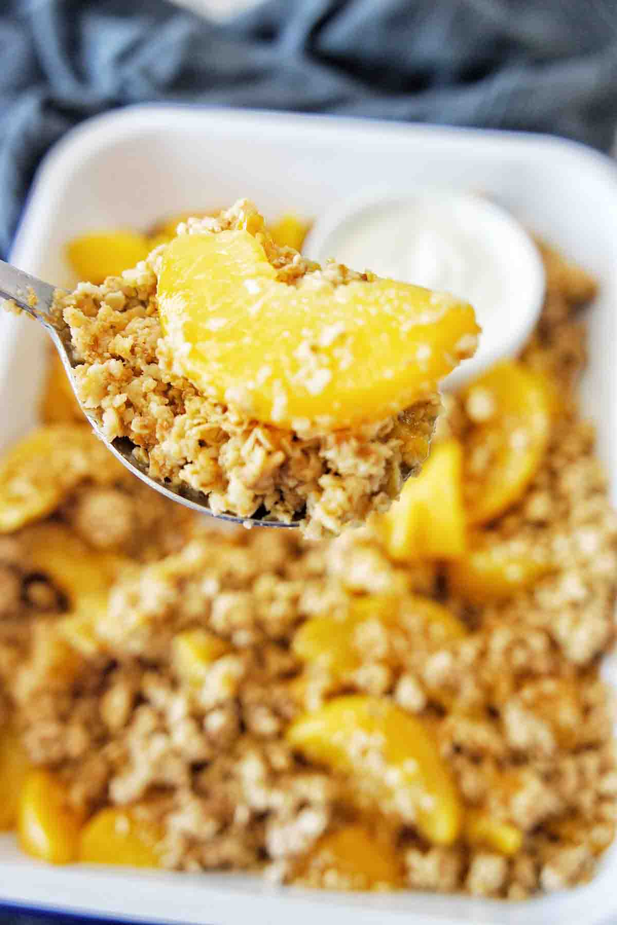Spoon holding peach crumble above white baking tray