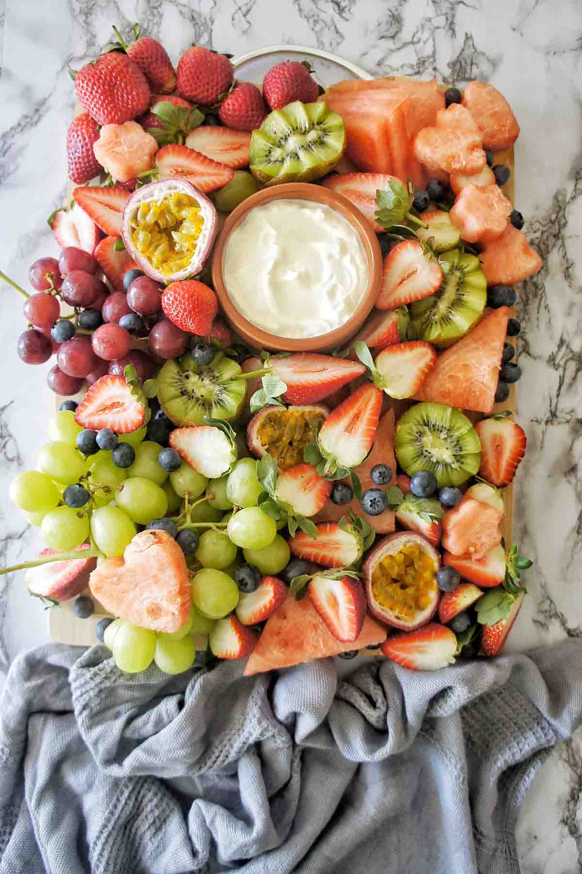 Fruit on a platter with a bowl of yoghurt in the centre