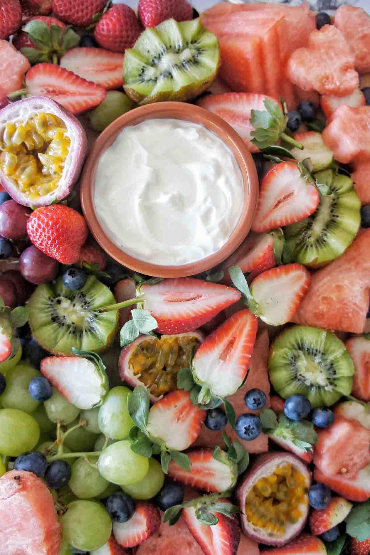 Bowl of yogurt on platter surrounded by fruit