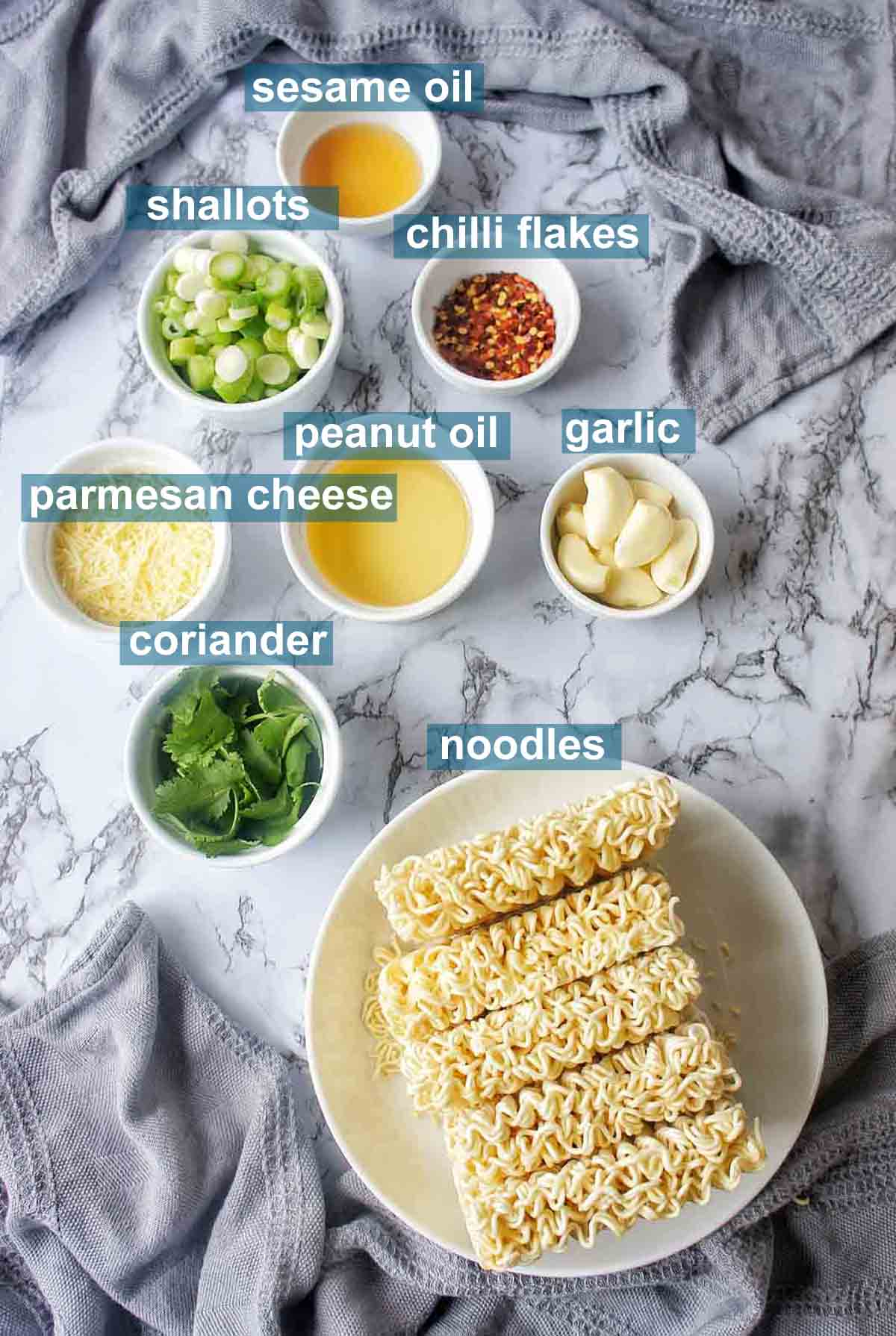 Garlic noodle ingredients on marble background with text labels