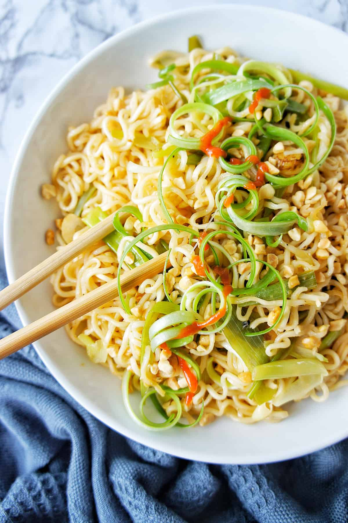 Ginger Scallion Noodles on a white plate with chopsticks