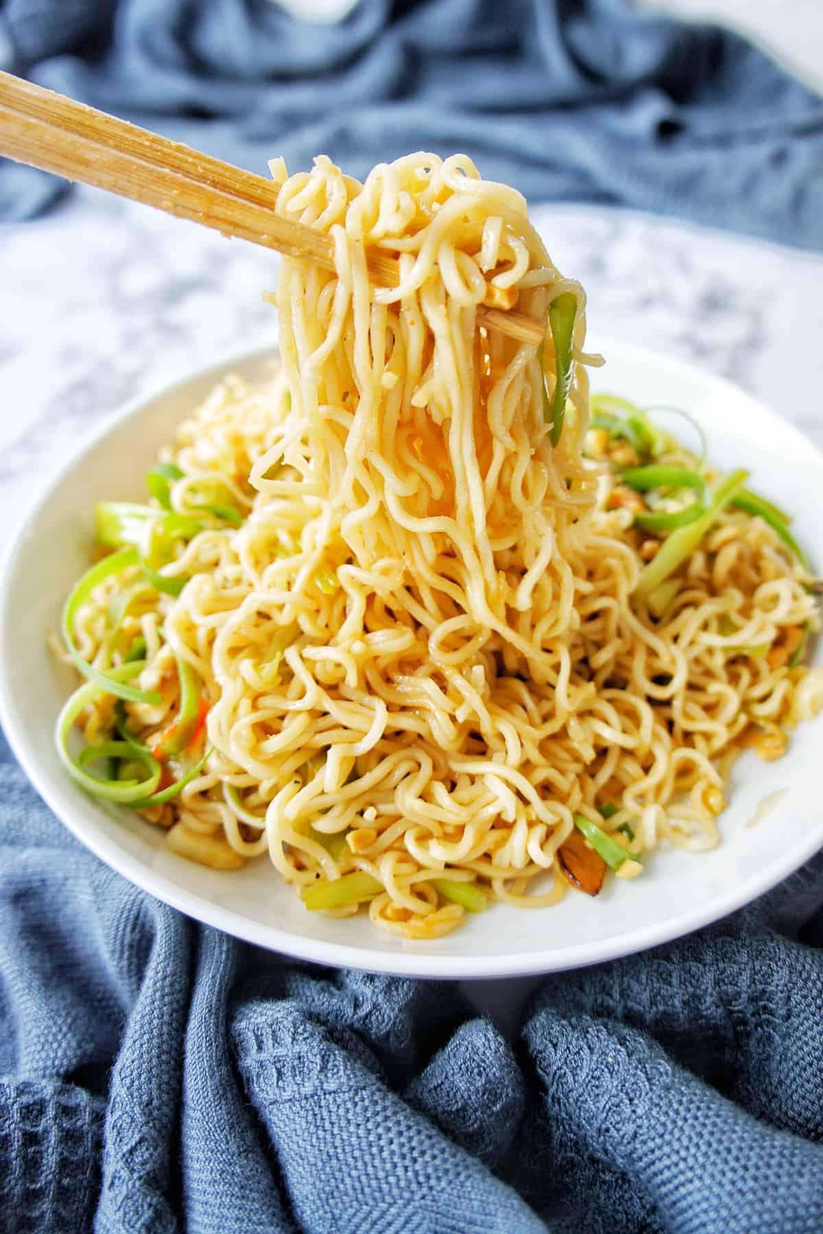 Chopsticks holding noodles over a bowl