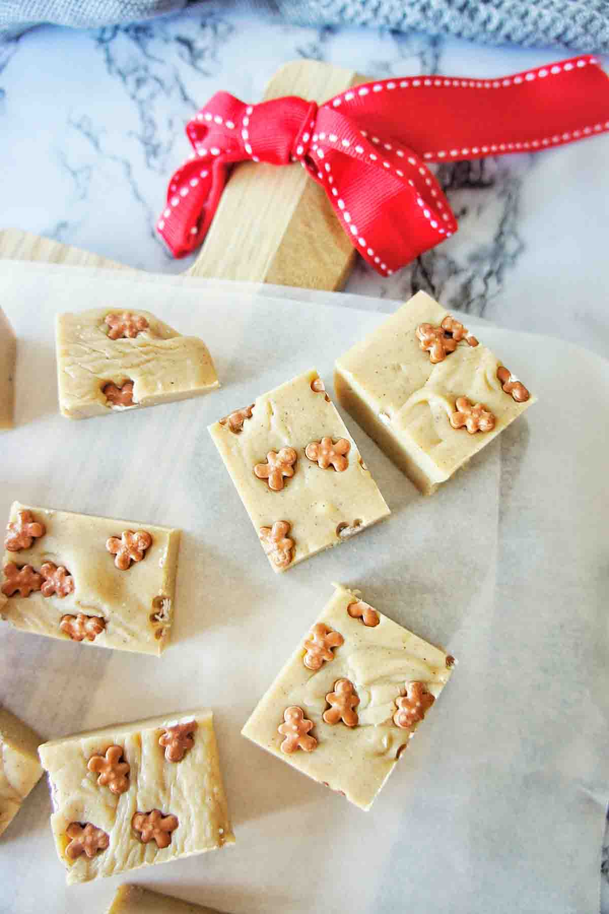 Gingerbread fudge cut into pieces on chopping board with baking paper