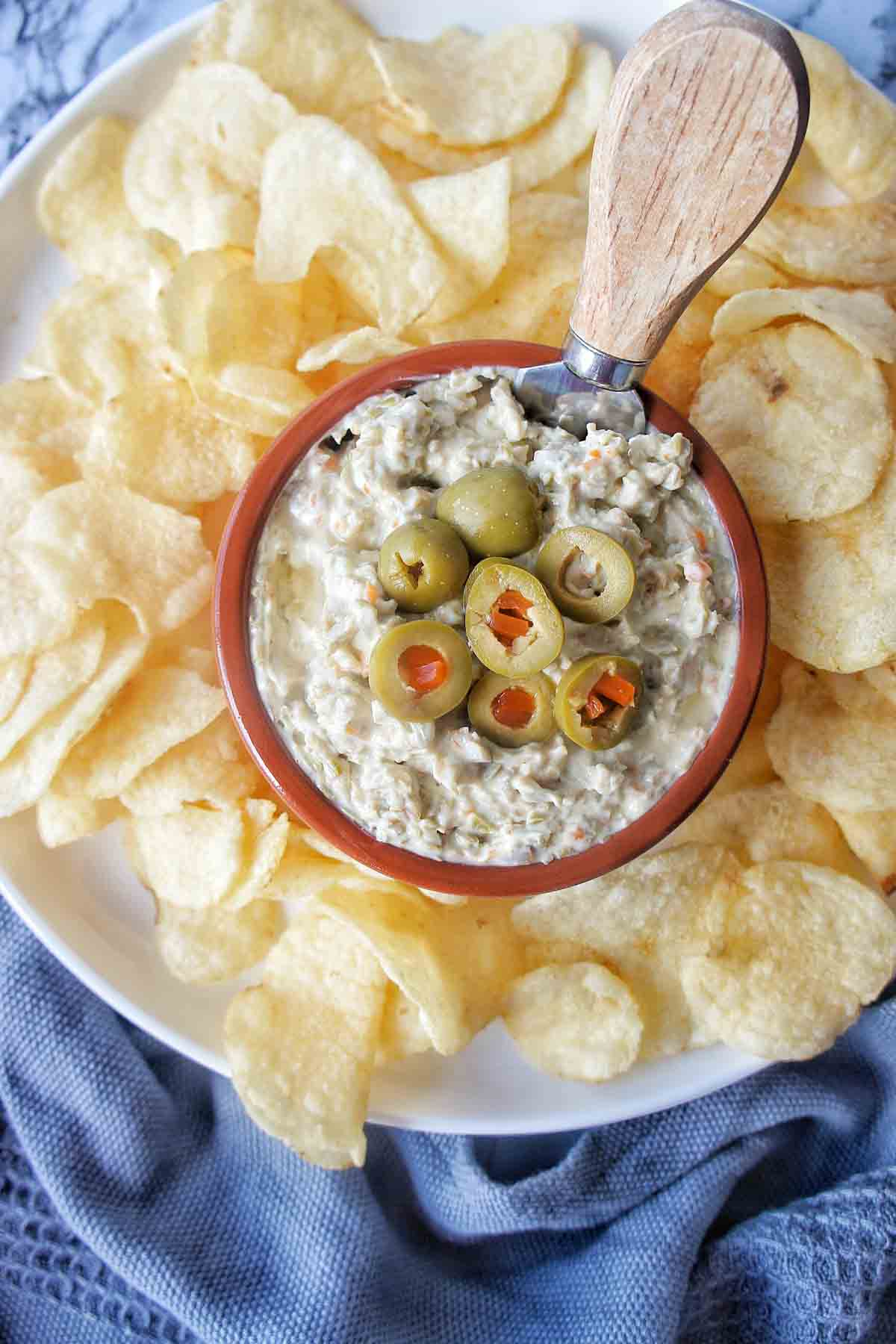 Green Olive Dip in a bowl on a white platter surrounded by chips