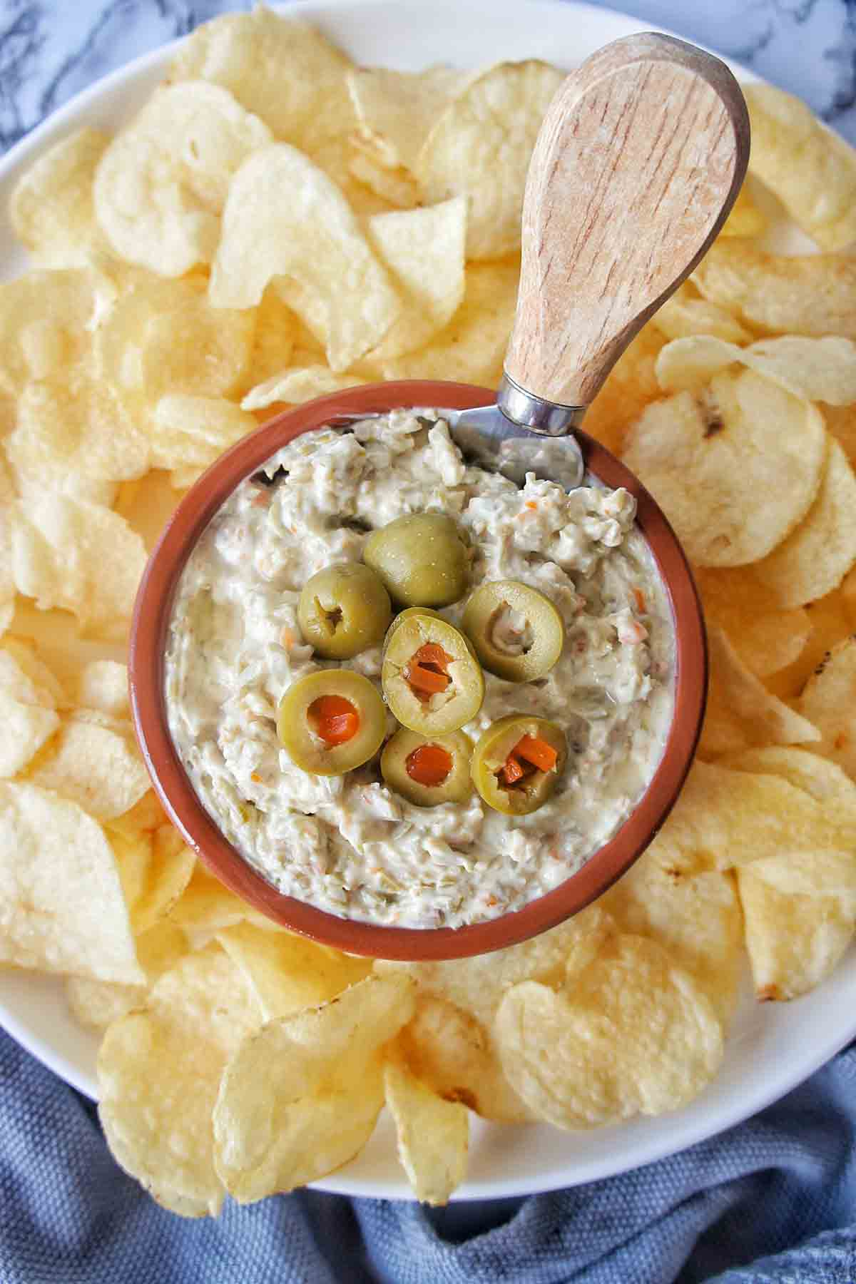 Green Olive Dip in a bowl surrounded by chips