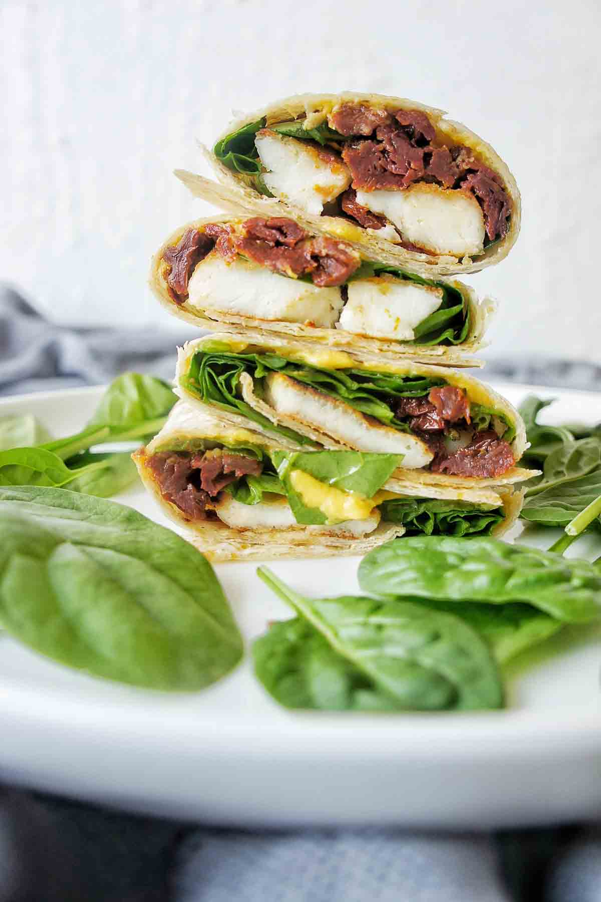 Haloumi wrap stack on a white plate with yellow sauce running down front