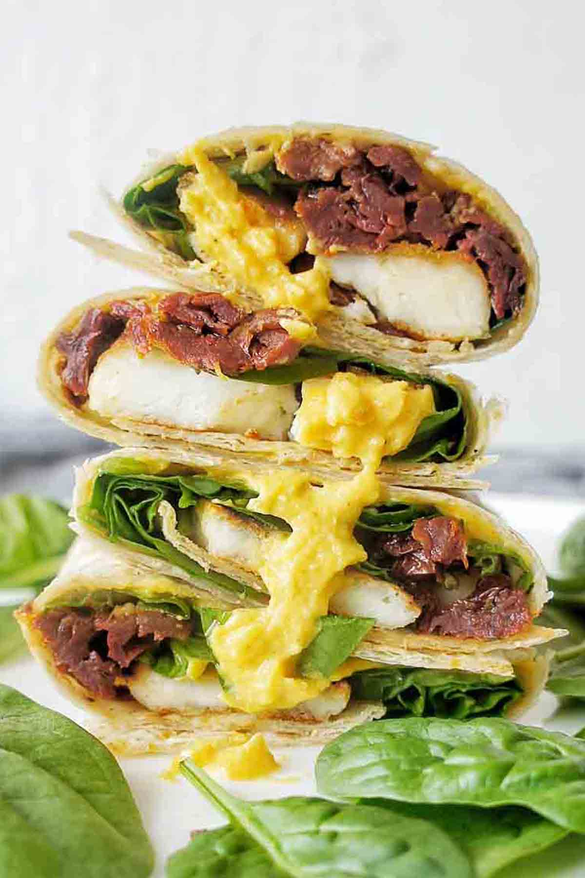 Haloumi wrap stack with pumpkin dip and spinach on a white plate