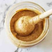 Almond Butter in a glass jar with lid off and stirrer inside