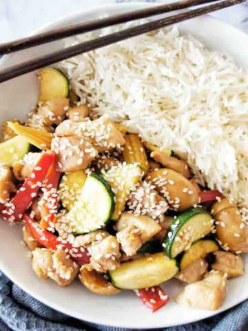 Honey Soy Chicken Stir Fry with rice in a white bowl with chopsticks on top