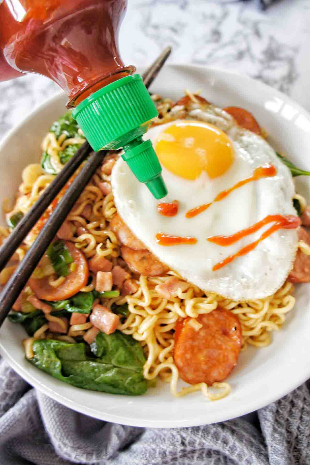 Sriracha sauce being poured onto fried egg on noodle bowl