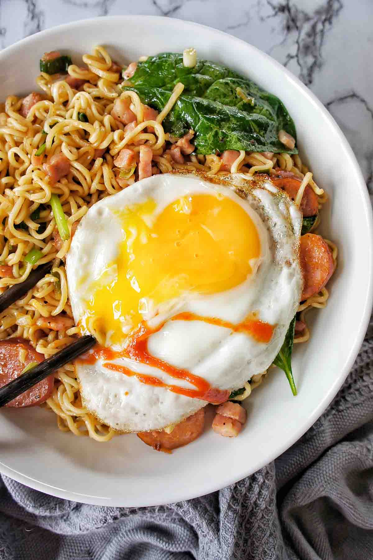 Frieg egg on top of bowl of noodles with chili sauce