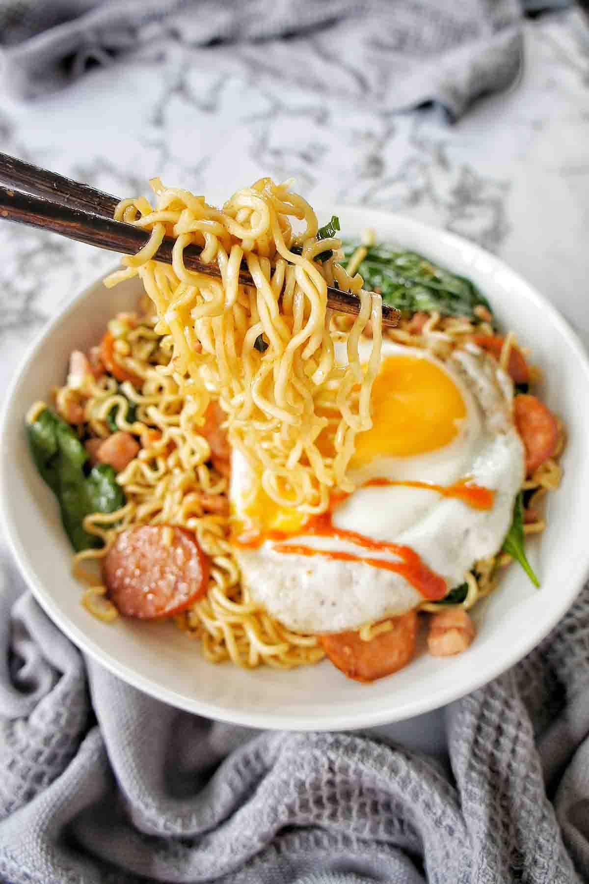 Chopsticks holding noodles above bowl of the same