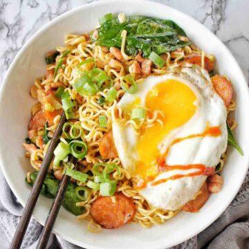 Runny fried egg on bowl of noodles with chopsticks