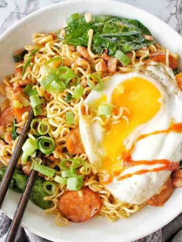 Runny fried egg on bowl of noodles with chopsticks