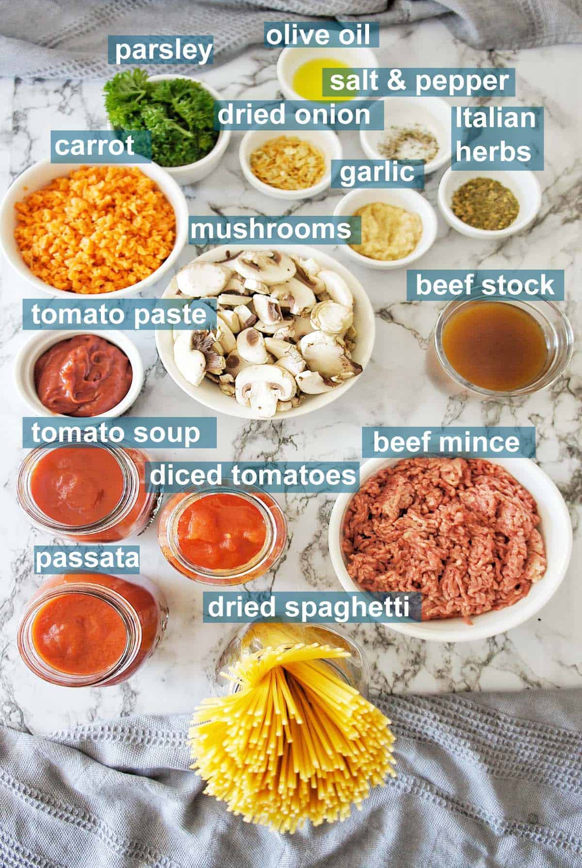 Ingredients for Spaghetti Bolognese on marble background with text overlay