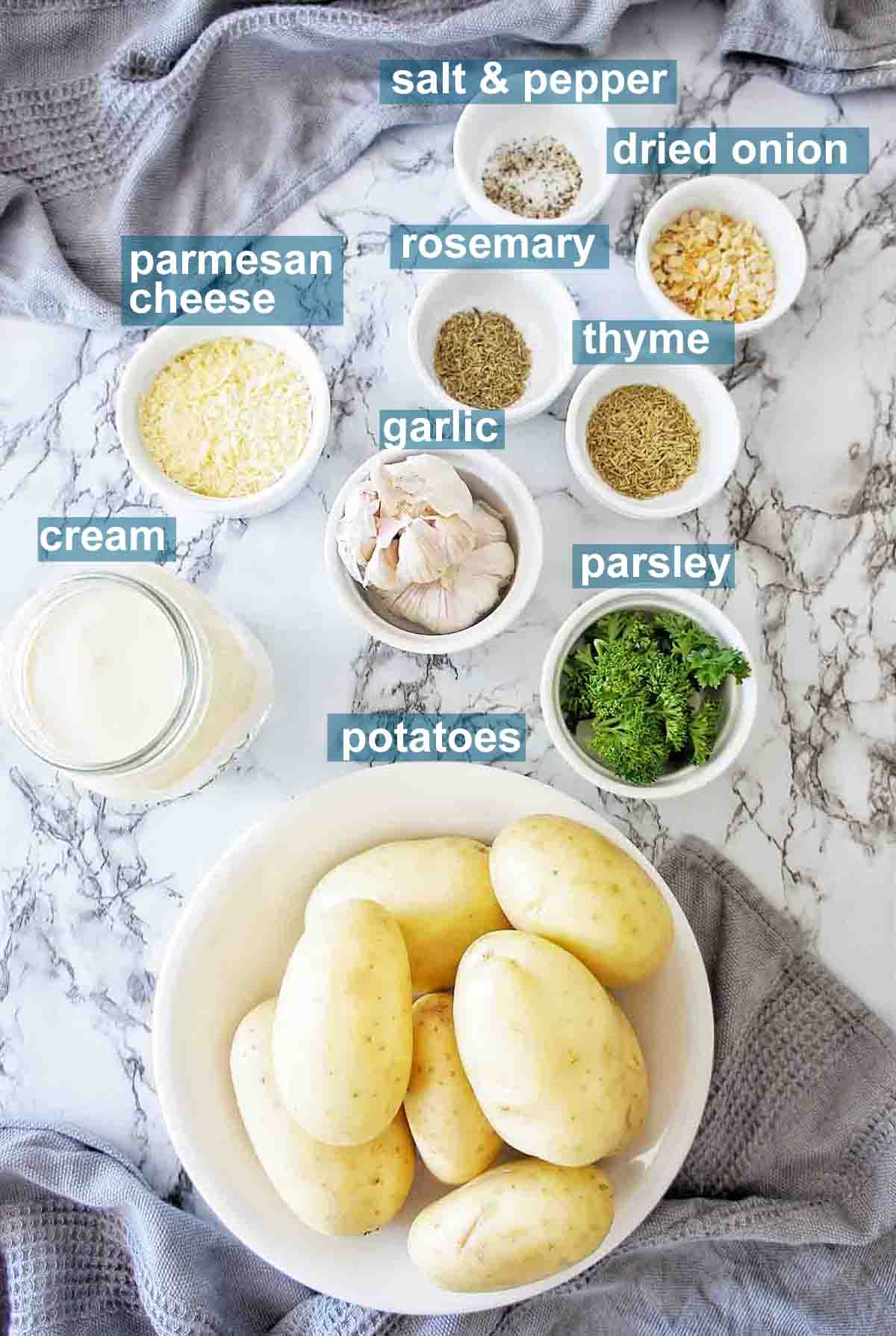 Ingredients for making creamy garlic potatoes with text over lay on a marble background
