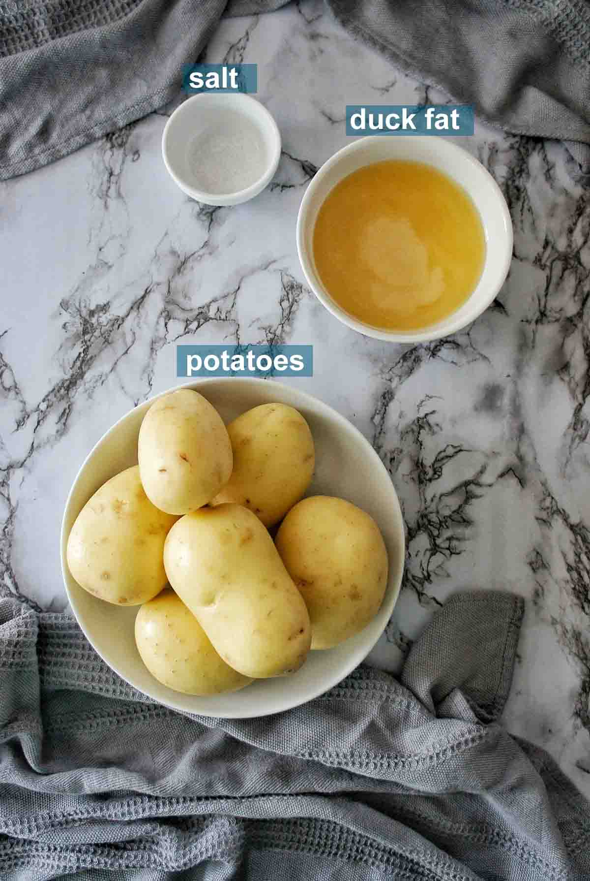 Ingredients for duck fat potatoes on a marble background with text labels