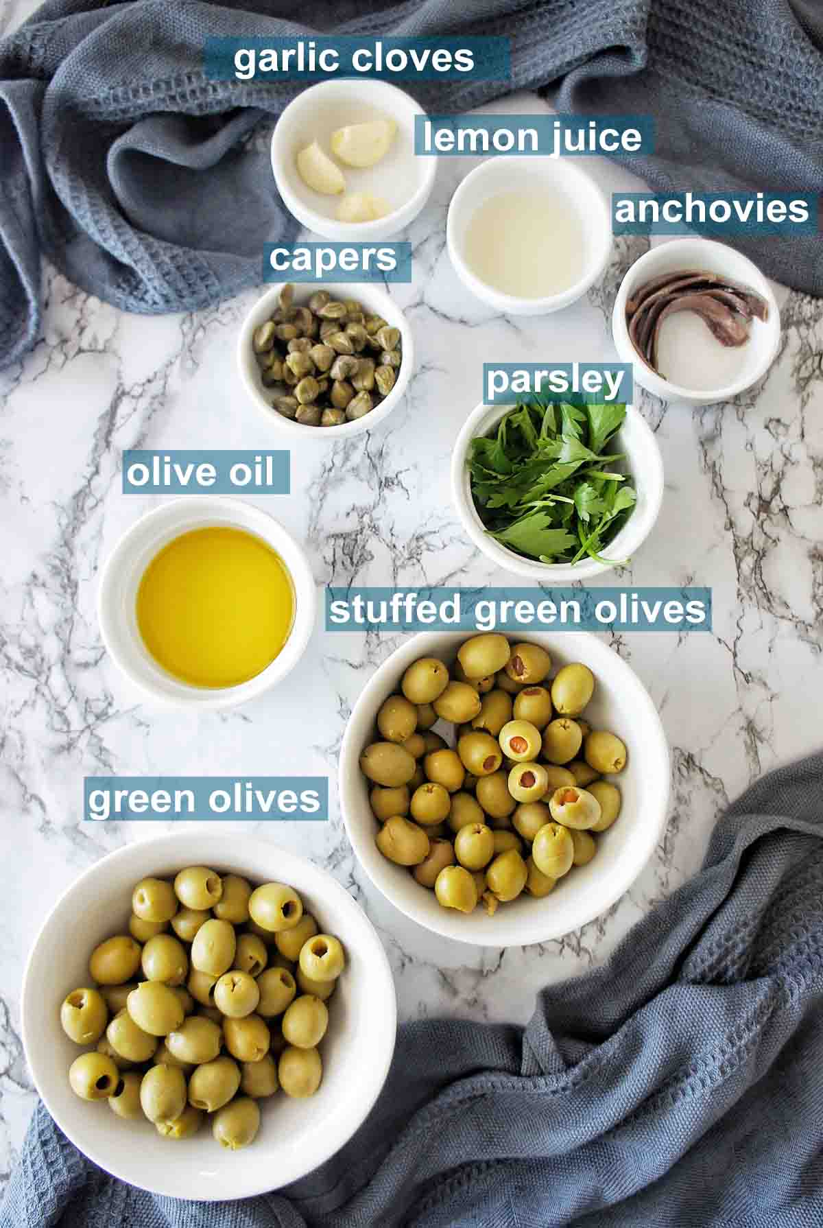 Ingredients for green olive tapenade set out with text overlay