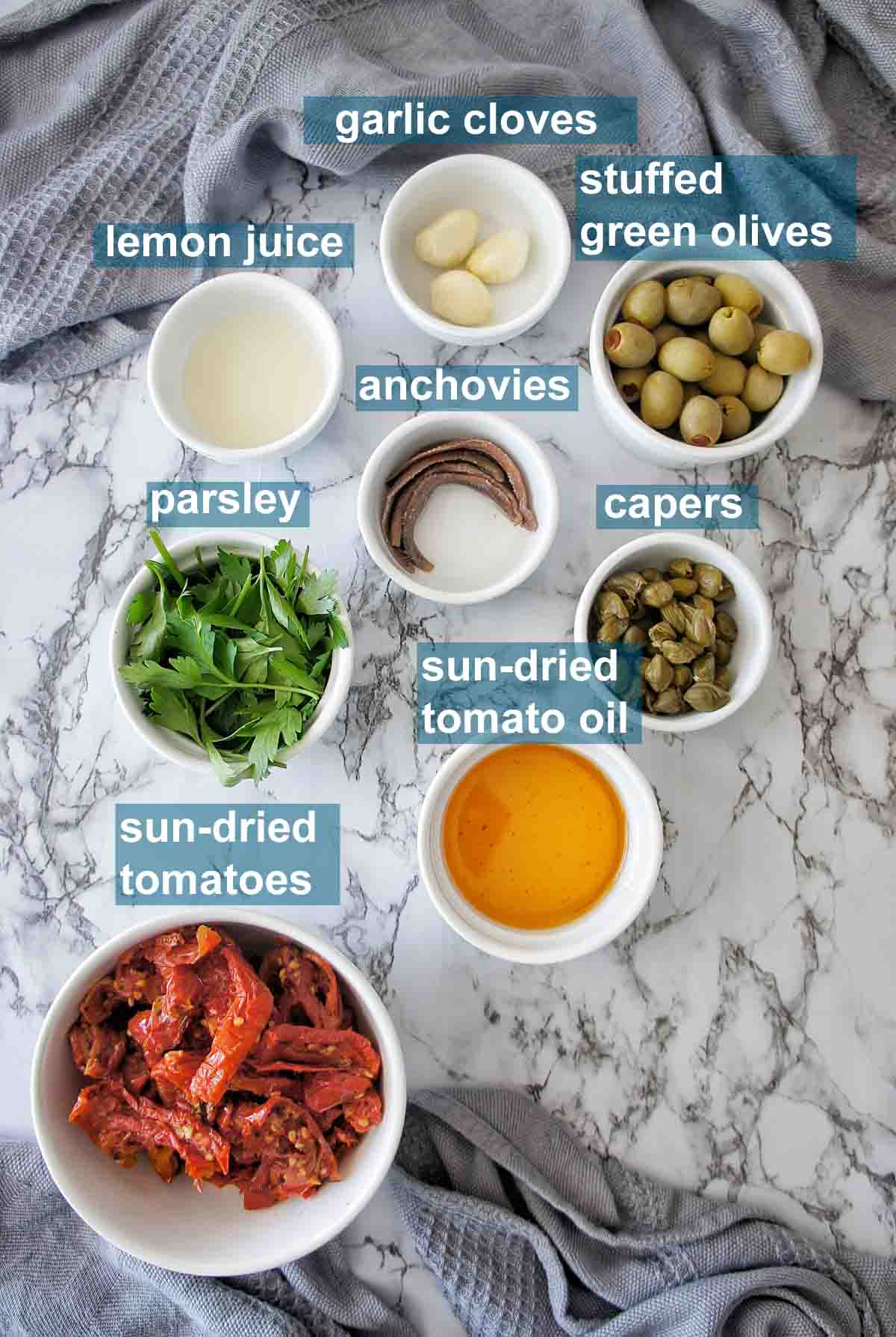 Ingredients for sun-dried tomato tapenade with text overlay