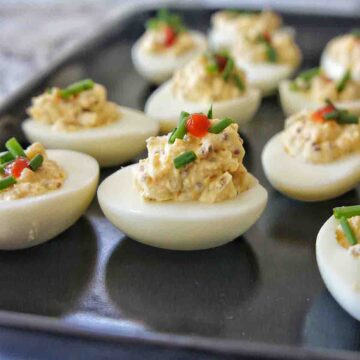 Instant Pot Deviled Eggs on a black plate showing height of toppings