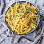 Garlic pasta in a large blue bowl with server