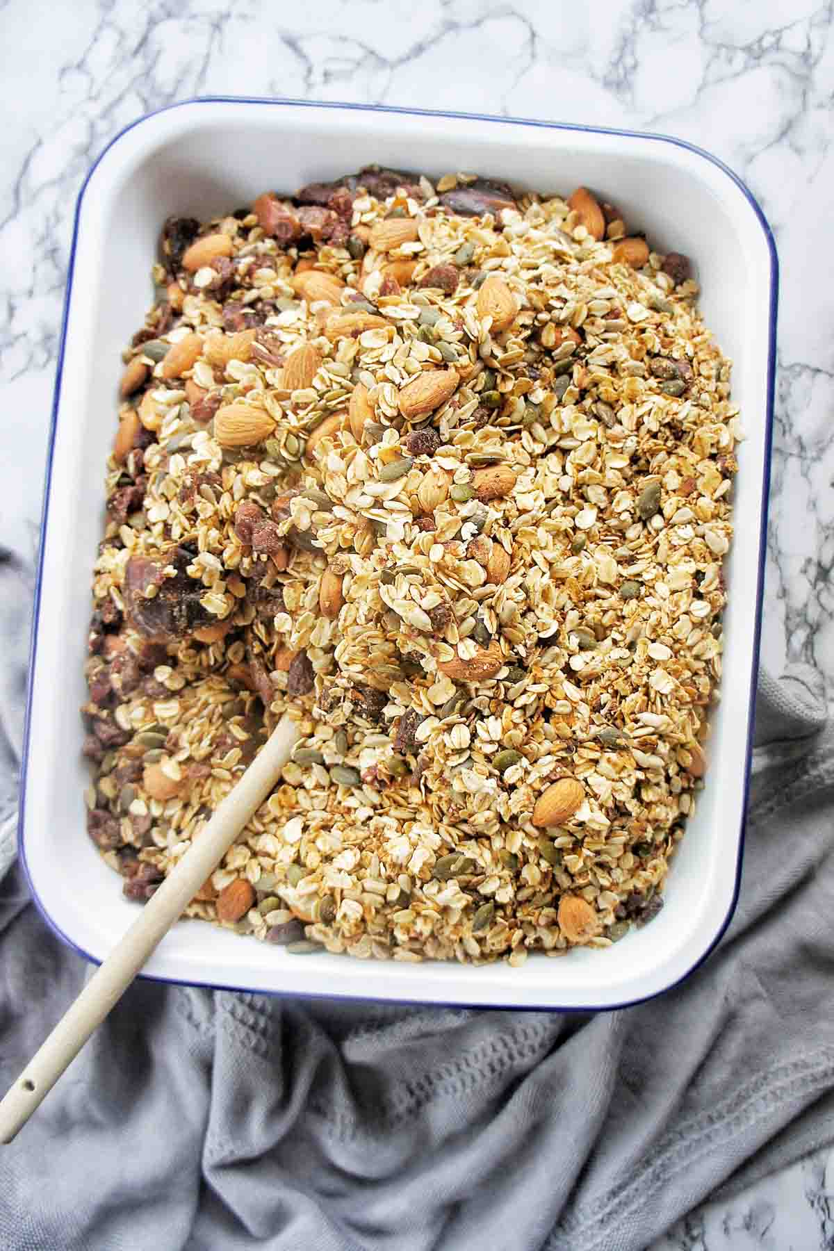 Pressure Cooker Granola in a white baking dish with wooden spoon