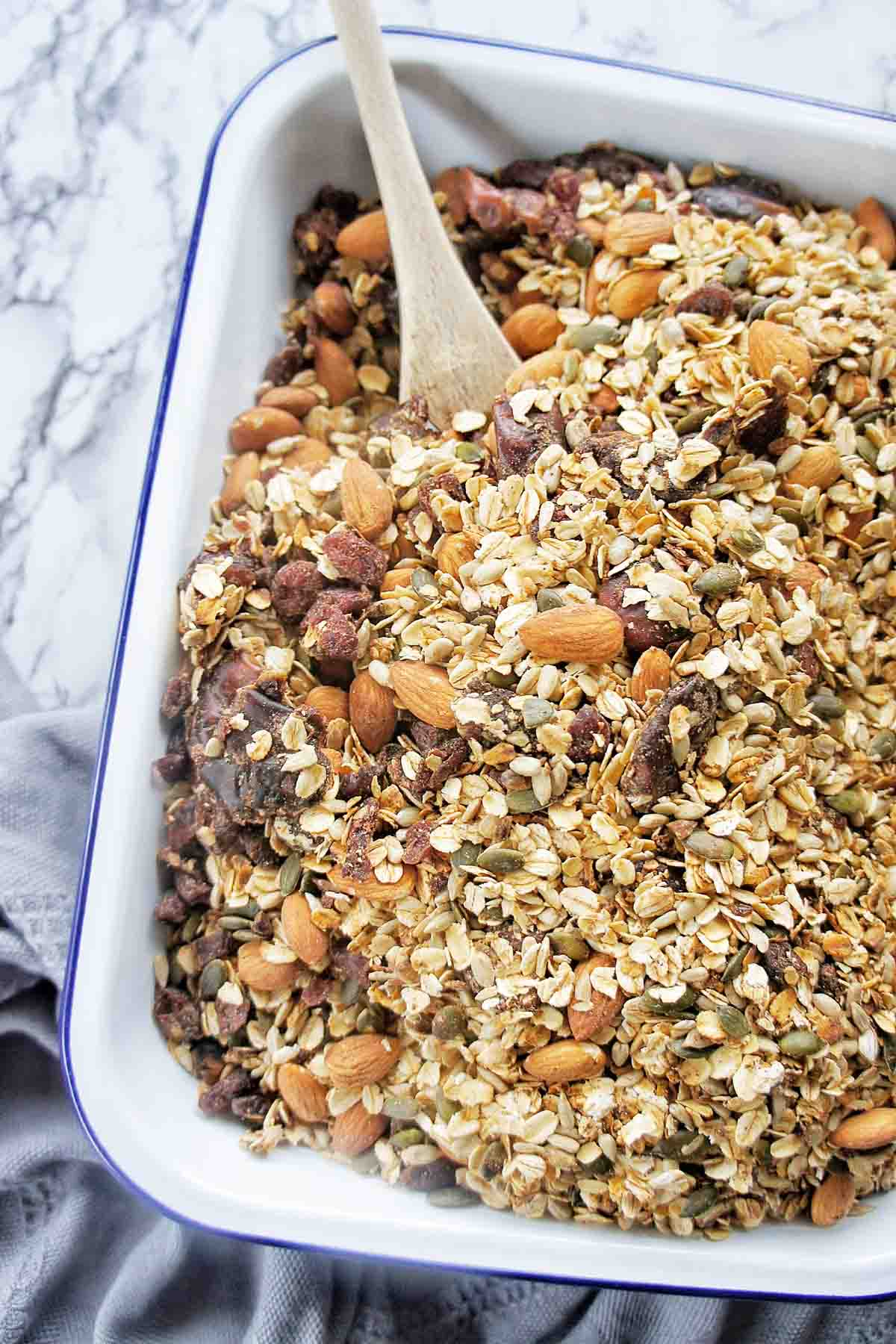 Instant Pot Granola in a white baking dish with wooden spoon