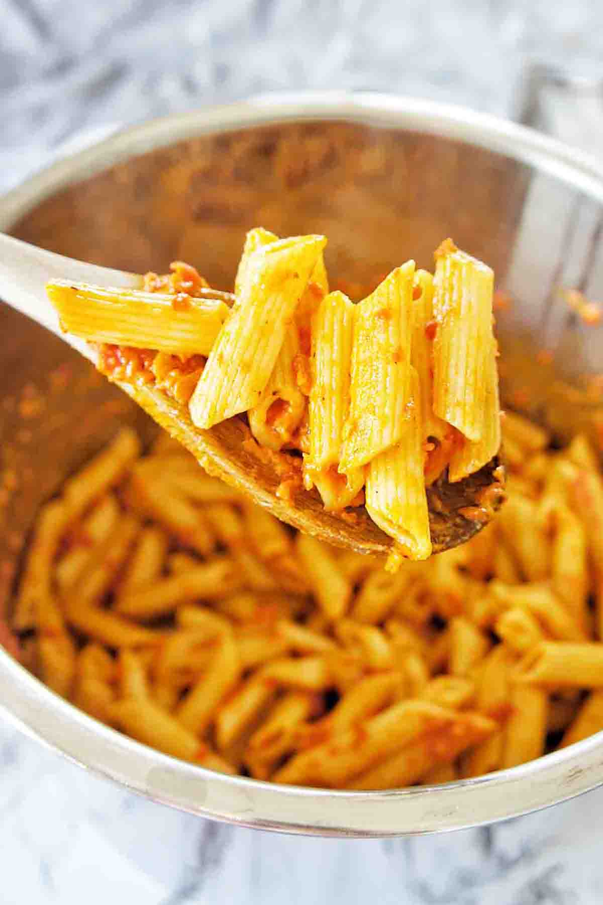 Wooden spoon holding cooked pasta with sauce above an instant pot