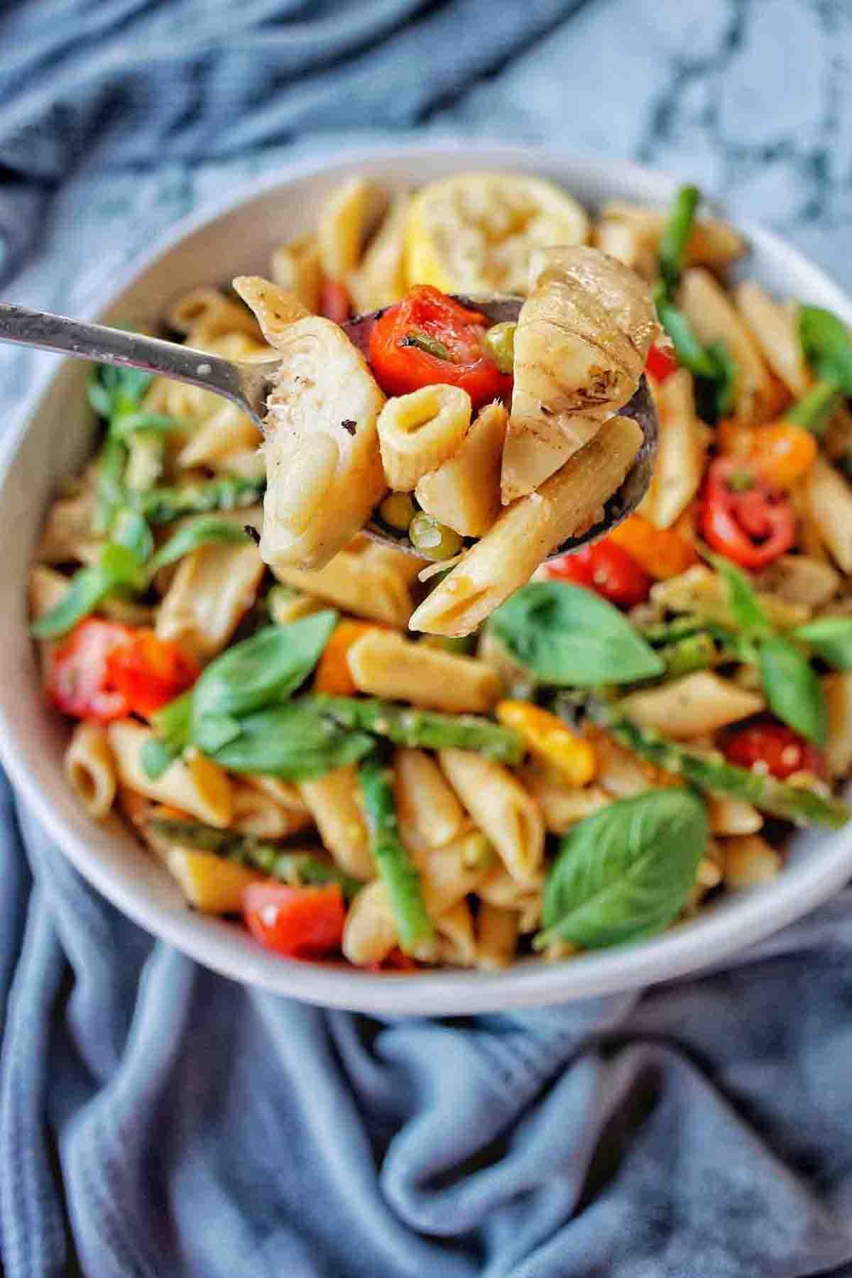 Spoon holding primavera pasta above bowl of the same