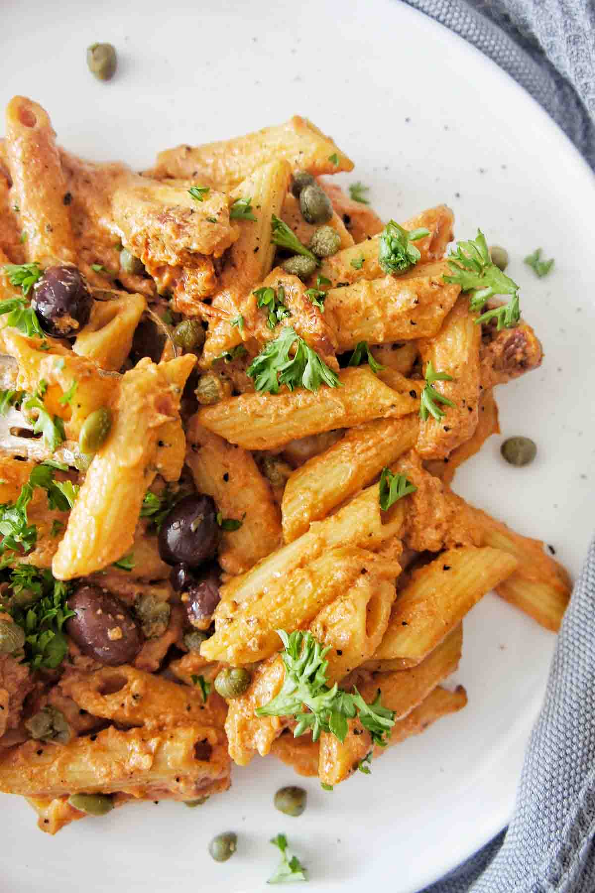 Penne pasta on a white plate with parsley, capers and olives