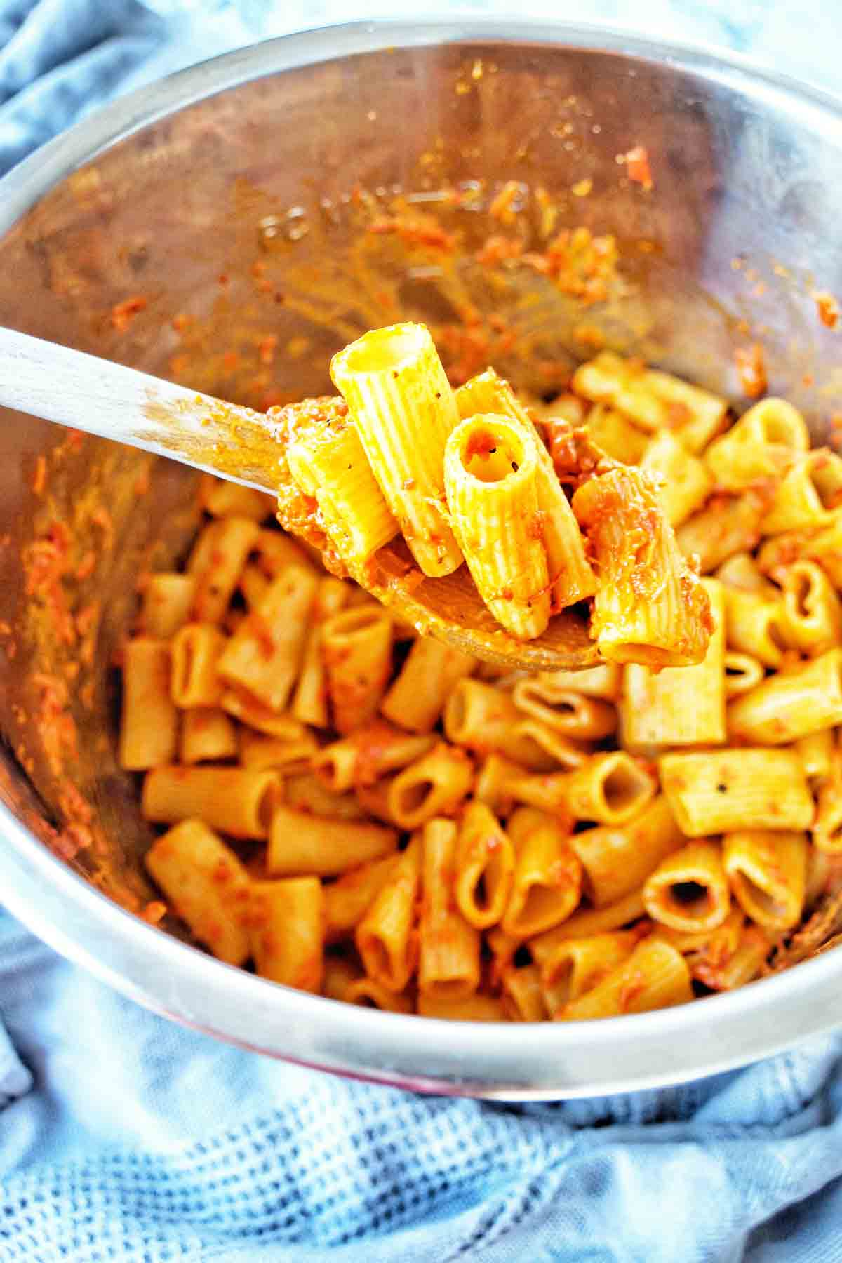 Wooden spoon holding rigatoni over Instant Pot bowl of the same