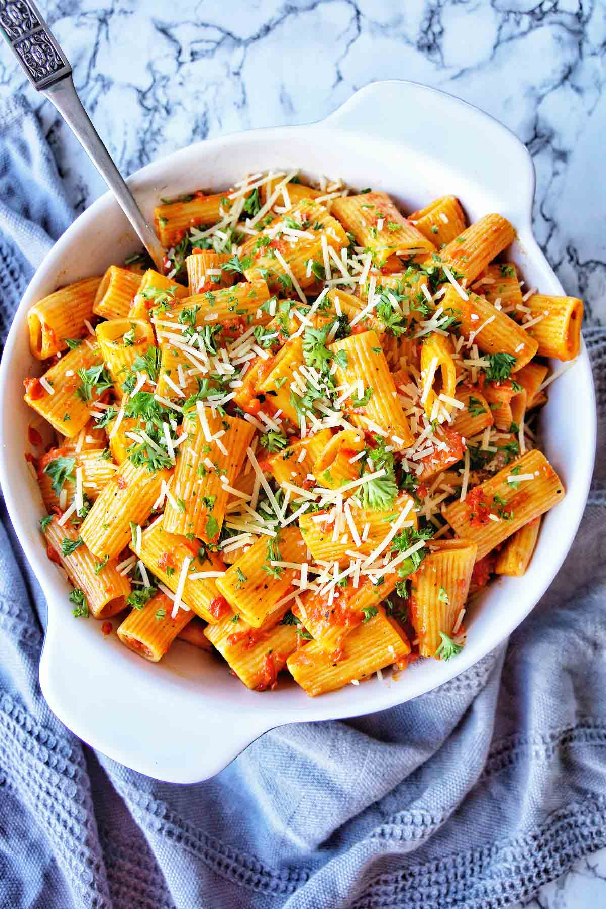 Rigatoni with jar sauce in a white bowl with server