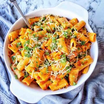 Rigatoni topped with parmesan and parsley in a white bowl with server