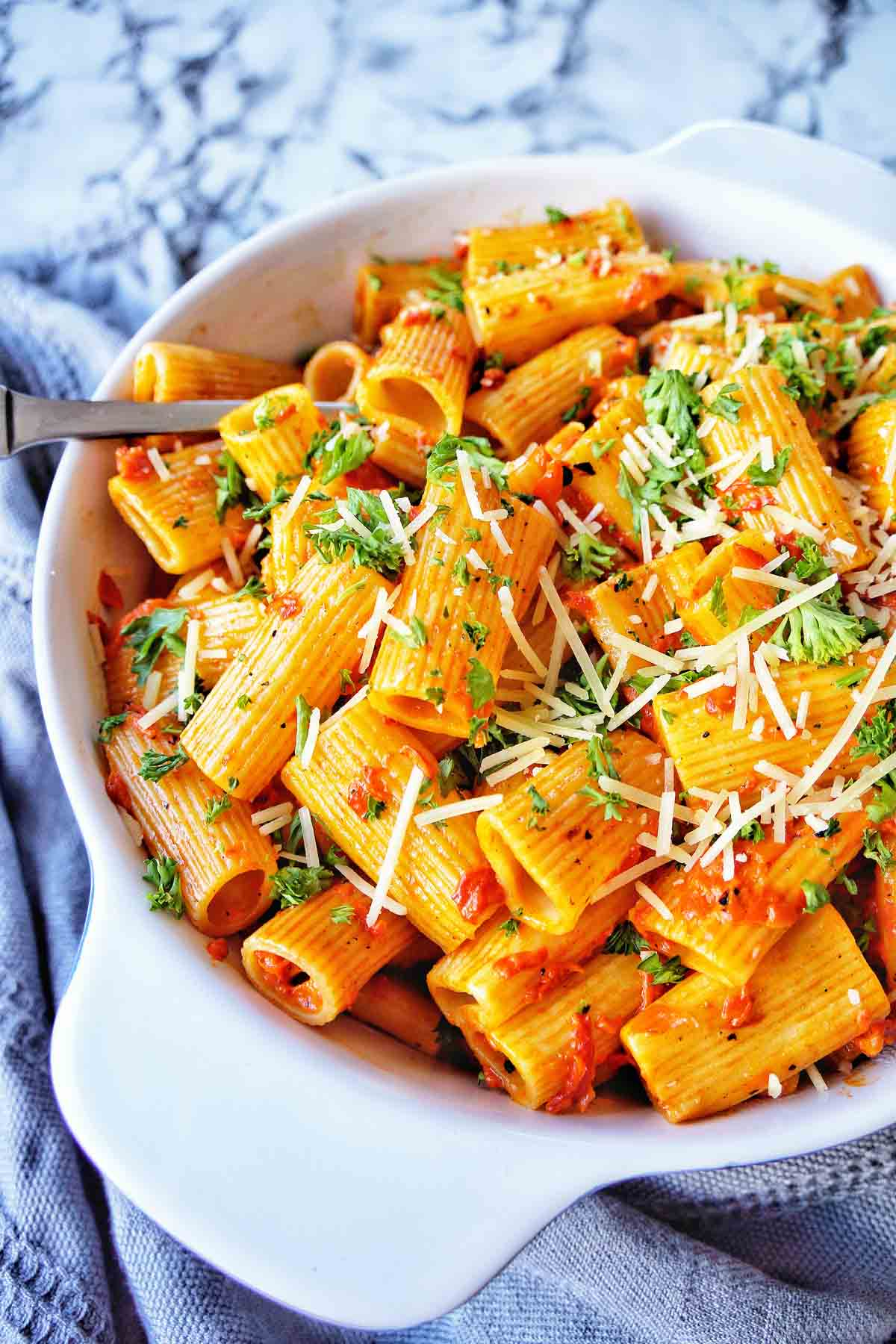 Rigatoni with sauce in a bowl with server