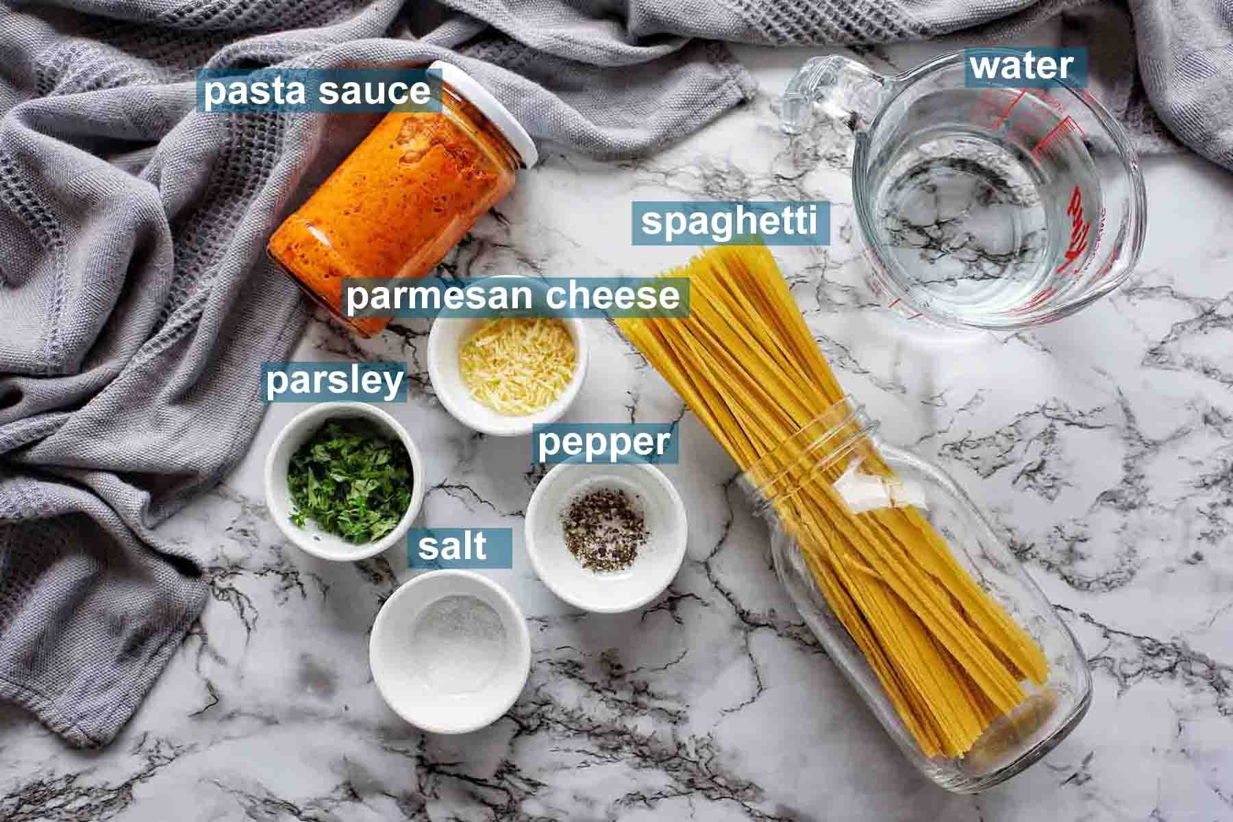 Instant Pot Spaghetti with Jar Sauce ingredients on marble background with text labels