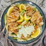 Italian Herb Chicken Thighs in a blue bowl with lemon