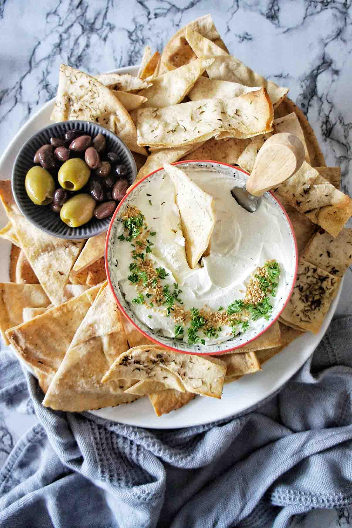 Labneh Dip on a platter with pita chips and olives
